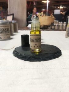 10 ml bottle of Petrichor Coatl Meztli Essence displayed on a slate square with other Huetzca Health products in the background.