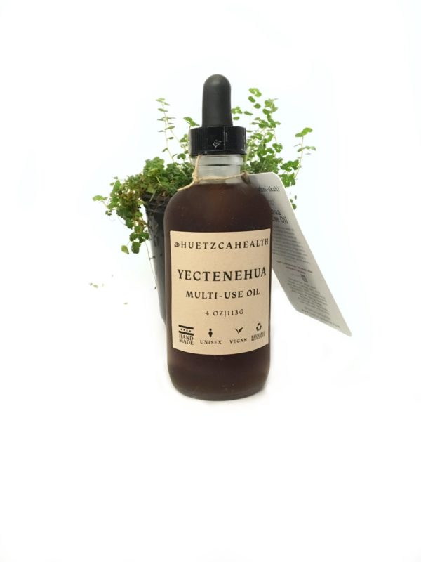 4 oz bottle of Yectenehua Multi-Use Oil on a white background with a string of pearl plant behind the bottle.